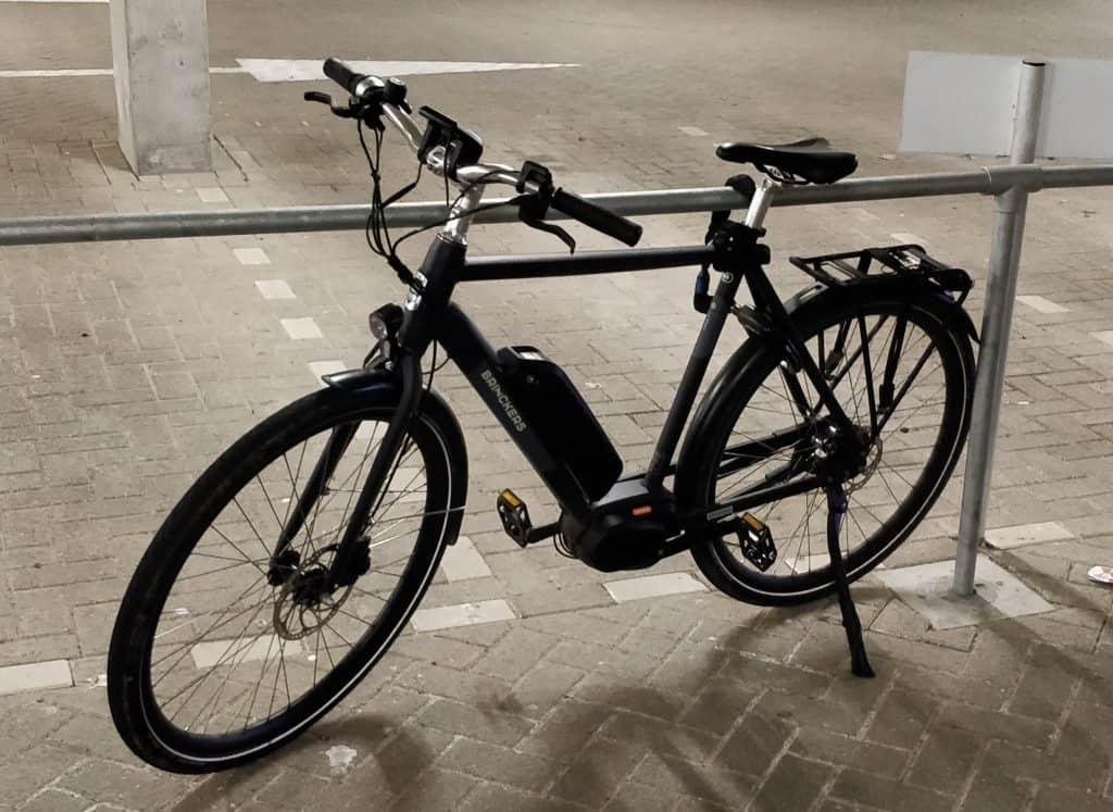 E-bike met kettingslot hoog aan een hek vastgemaakt